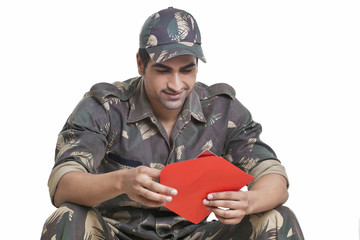 Male soldier holding greeting card over white background