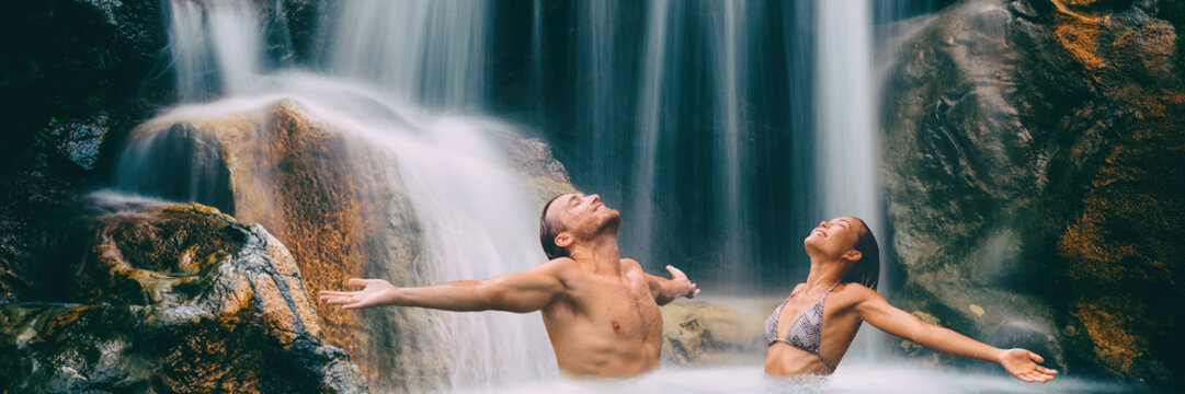 Nature couple relaxing under waterfall with open arms in freedom banner. People enjoying water falling in natural pool in tropical nature. Wellness, health and spa. Wide landscape crop for panorama.