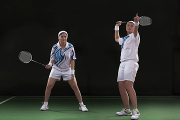 Young women playing badminton over black background
