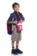 Smiling school boy standing with book bag and water bottle against white background