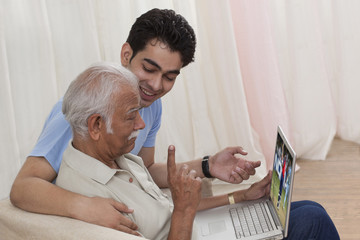 Grandson and grandfather with a laptop