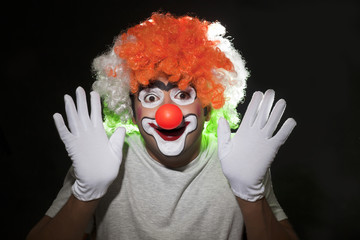 Close-up of male clown performing over black background