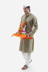 Maharashtrian man holding a Ganesh idol