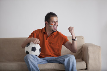 Excited young man with soccer ball cheering while sitting on sofa at home