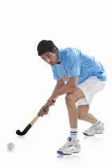 Full length of sportsman playing hockey isolated over white background