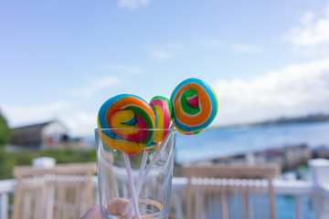 Rainbow lollies held up against a blue sky by the sea in Cornwall