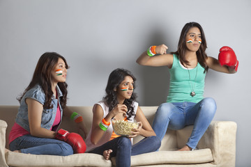 Young female friends watching boxing match together at home