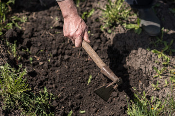 Man digs the earth with a hoe