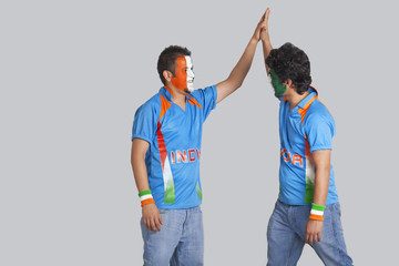 Male cricket fans in jerseys giving a high-five to each other over colored background