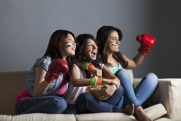 Exhilarated young female friends watching boxing match together at home