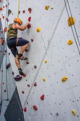 Muskelkraft - Mann klettert auf Kletterwand