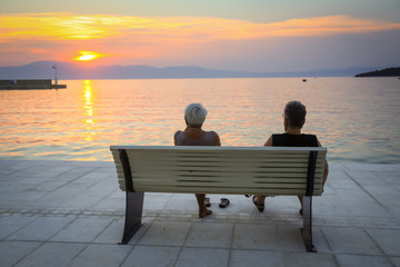 Two woman enjoys sunset on the bench