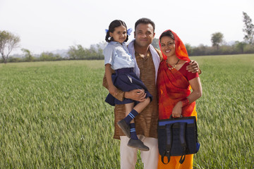 Portrait of a happy family of three standing together with field in background