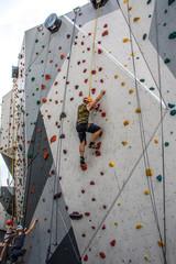 Mann klettert mit Händen und Füßen auf Kletterwand - Bergsteigen üben