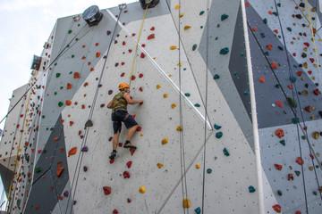 Mann klettert gesichert auf Kletterwand - Bergsteigen üben