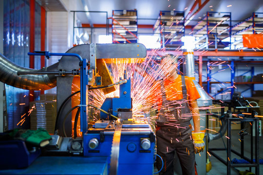 A male mechanic working on welding machine in the Industrial production of metal products. Sparks fly out of under the parts. Concept theme repair, mechanics, production, industry. Unrecognizable face