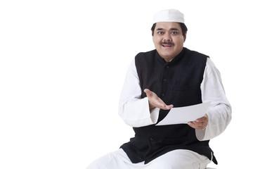 Portrait of mature politician holding document
