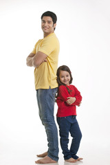 Portrait of smiling young father and daughter standing over white background