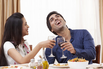 Young man laughing while having wine with his girlfriend at restaurant