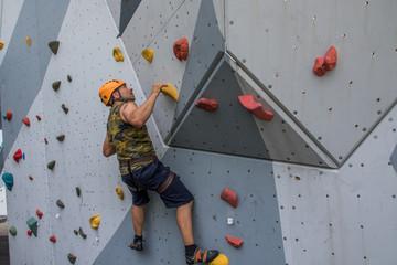 Mann mit Helm beim Bouldern auf Kletterwand, Überhang