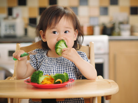 baby girl eating  vegetable at home