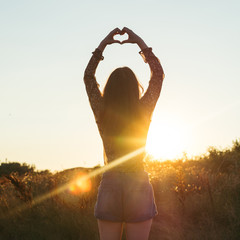 Young hippie woman sends heart shaped greeting to the Sun