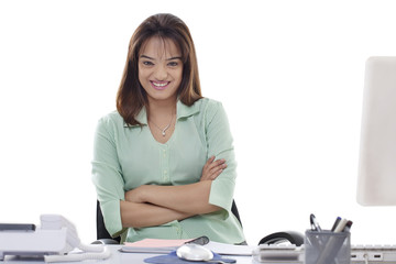 Portrait of smiling young businesswoman with arms crossed at office