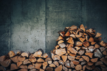 chopped logs for winter fire. Pile of firewood against old wooden fence
