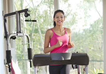 Young woman working out on treadmill
