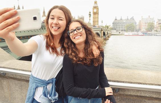 Happy smiling pretty teenage girls taking selfie at Big Ben, London