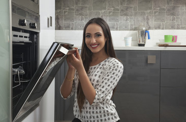 Young woman opening oven door
