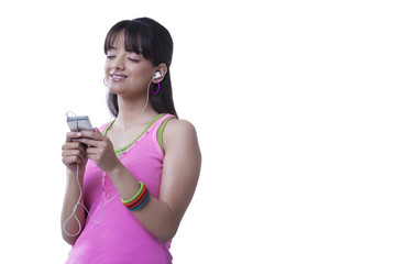 Relaxed young woman enjoying music over white background