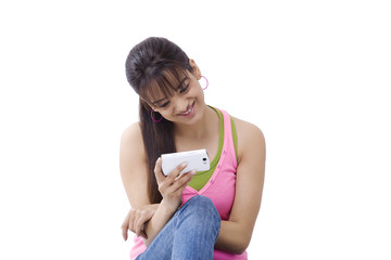 Smiling young woman reading text message over white background