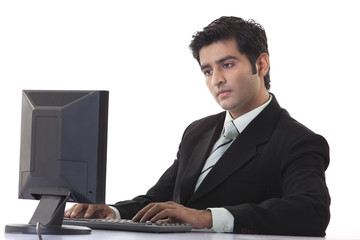 Young businessman using computer at desk