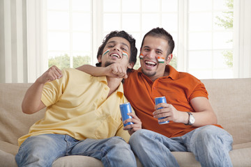Portrait of excited young male friends sitting on sofa with tin cans
