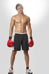 Full length portrait of shirtless boxer wearing boxing gloves against white background