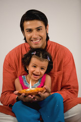 Girl holding a diya with her father