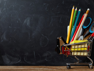 Trolley with school supplies on the background of a board with space for text