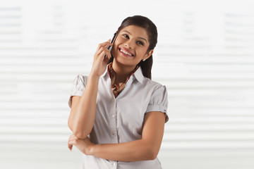 Pretty young business woman smiling while attending phone call