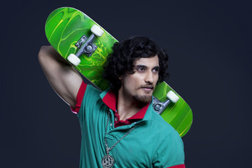 Close-up of young man holding skateboard behind head against black background