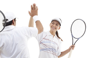 Excited tennis players doing high five isolated over white background