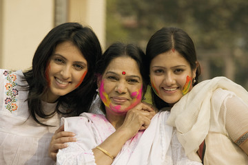 Mother and daughters celebrating Holi