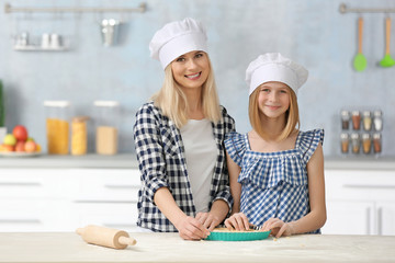 Mother and daughter cooking on table in kitchen