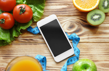 Mobile phone and healthy food on wooden table. Weight loss concept