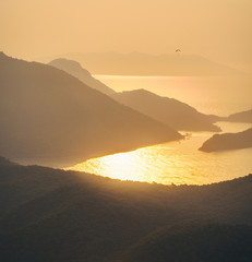 Wall Mural - Beautiful seascape with silhouettes of mountain ridges, water, islands, and orange sky in summer at bright sunset. Amazing view from the mountain peak on Oludeniz, Turkey. Mountain seashore. Travel