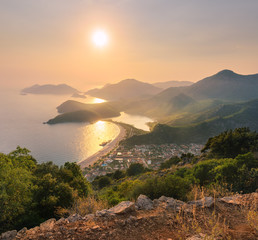 Wall Mural - Mountain landscape at sunset. Beautiful seascape with mountains, water, islands, city and orange sky with sun in summer. Amazing view from the mountain peak on Oludeniz, Turkey. Mountain seashore