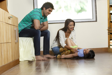 Happy woman playing with daughter while man sitting besides