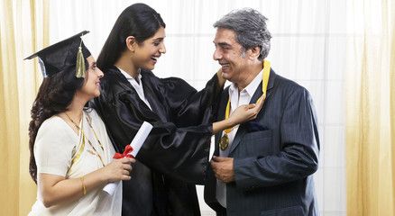Girl putting her medal around her fathers neck