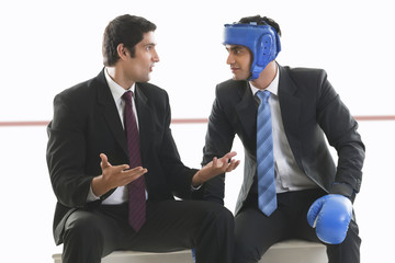 Businessman with boxing gloves listening to his colleague