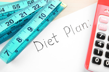 Diet concept. Measuring tape, calculator and diet plan, closeup
